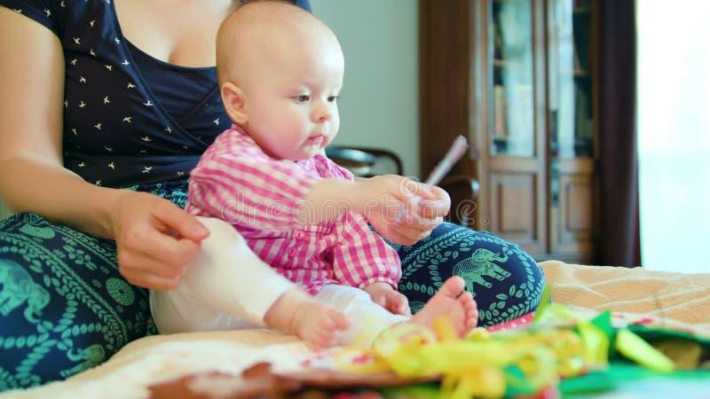 Bebê e mãe e jogo com um brinquedo foto de stock