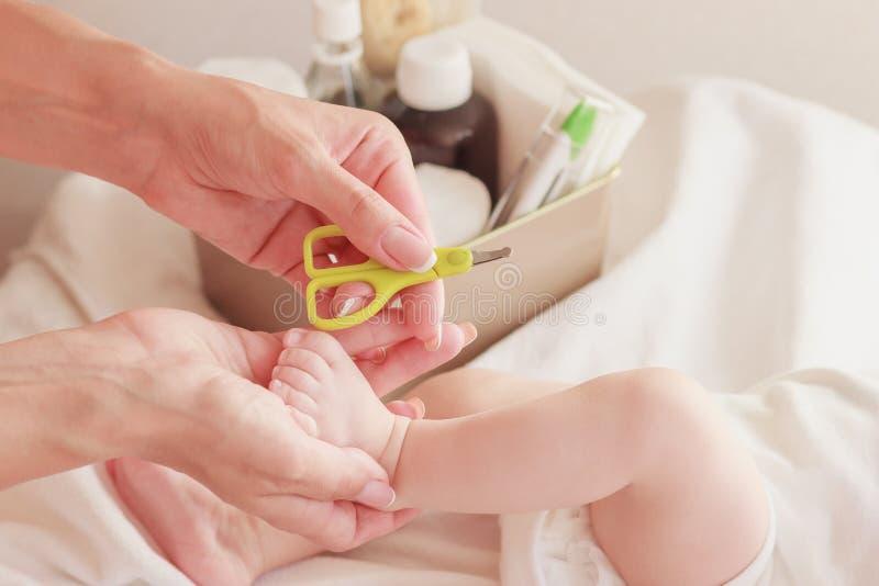 Bebê e mãos da mãe com as tesouras de um bebê, dentro, fundo borrado fotografia de stock