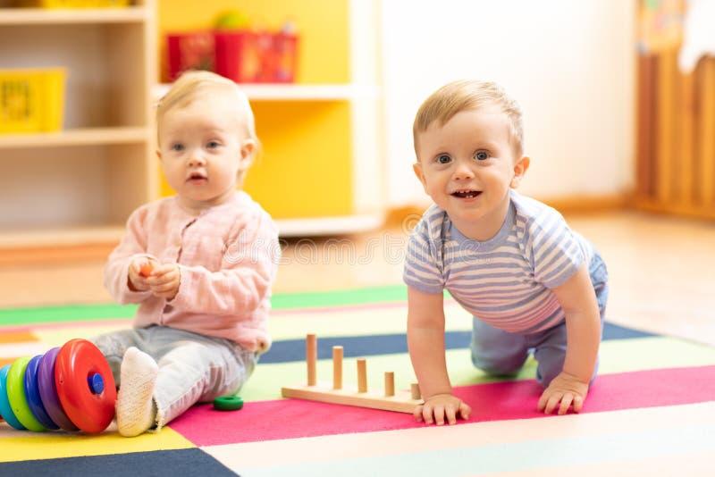 Bebê e menina engraçados de rastejamento na sala do jogo no berçário imagem de stock