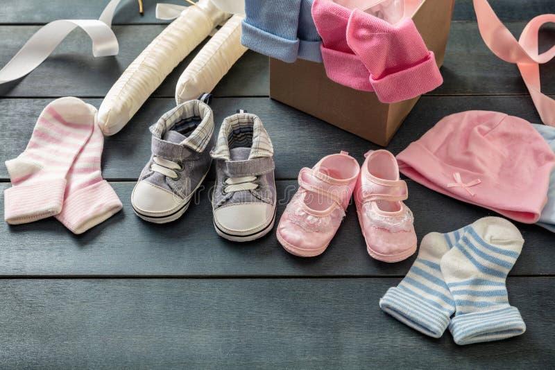 Bebê e sapatas e peúgas da menina no fundo de madeira azul foto de stock royalty free