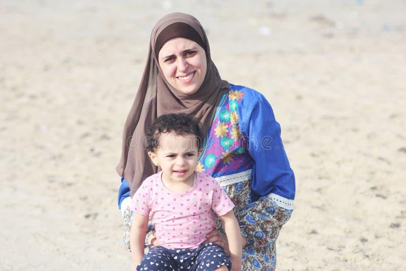Bebê egípcio muçulmano árabe feliz engraçado com sua mãe foto de stock