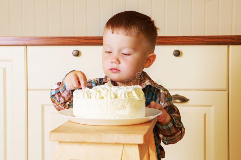 Bebê em casa com um bolo grande fotografia de stock