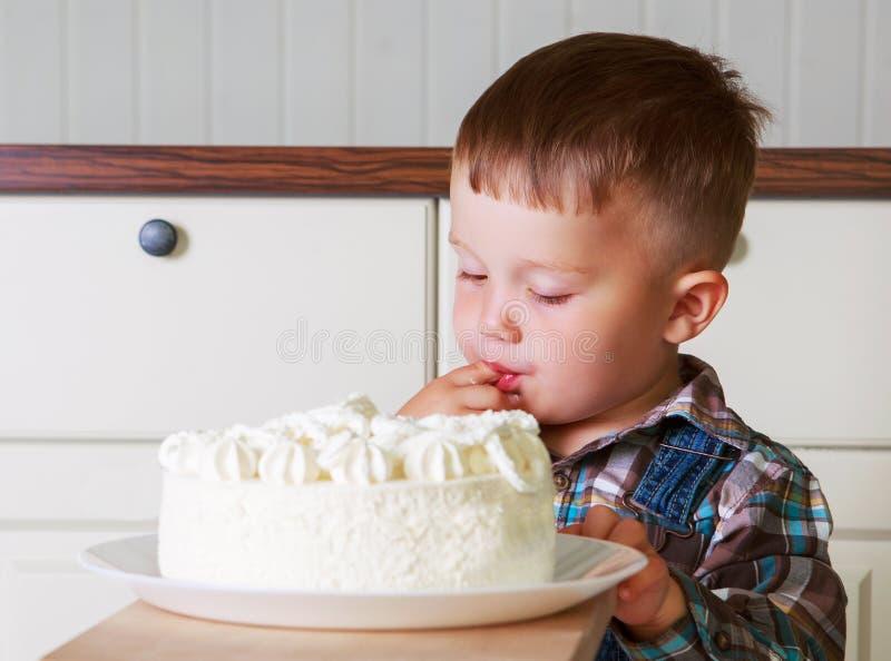 Bebê em casa com um bolo grande imagens de stock royalty free