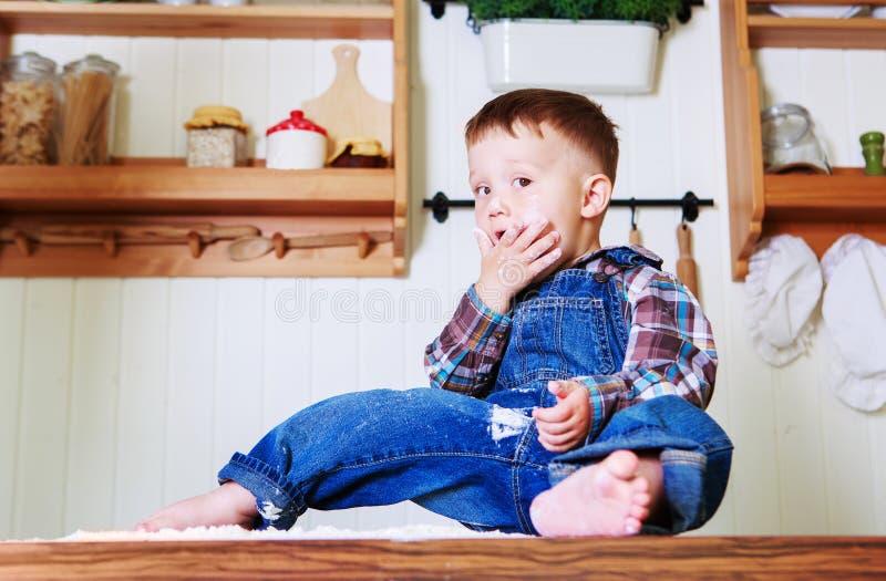 Bebê em casa na cozinha com farinha imagem de stock