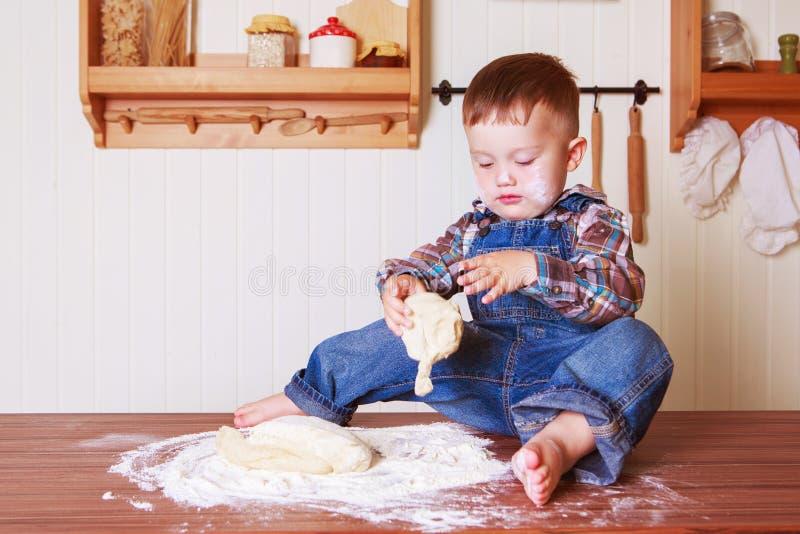 Bebê em casa na cozinha com massa foto de stock