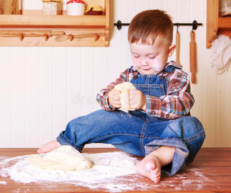 Bebê em casa na cozinha com massa imagem de stock royalty free