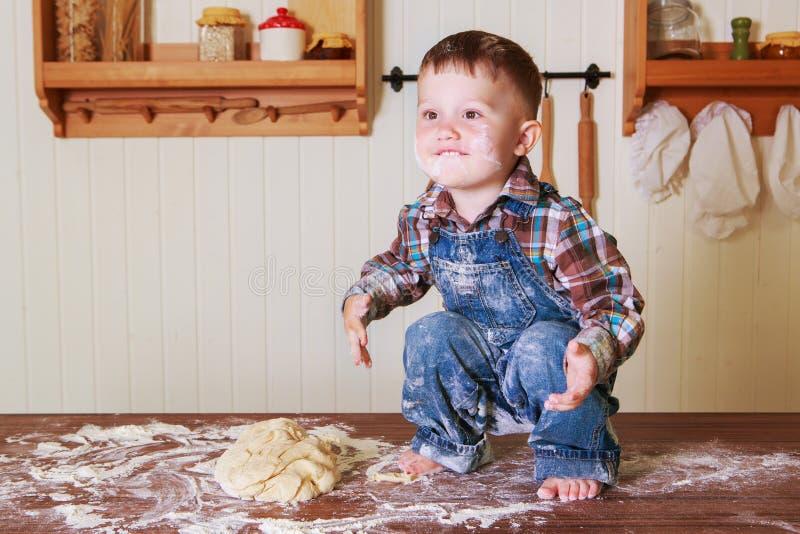 Bebê em casa na cozinha com massa imagem de stock