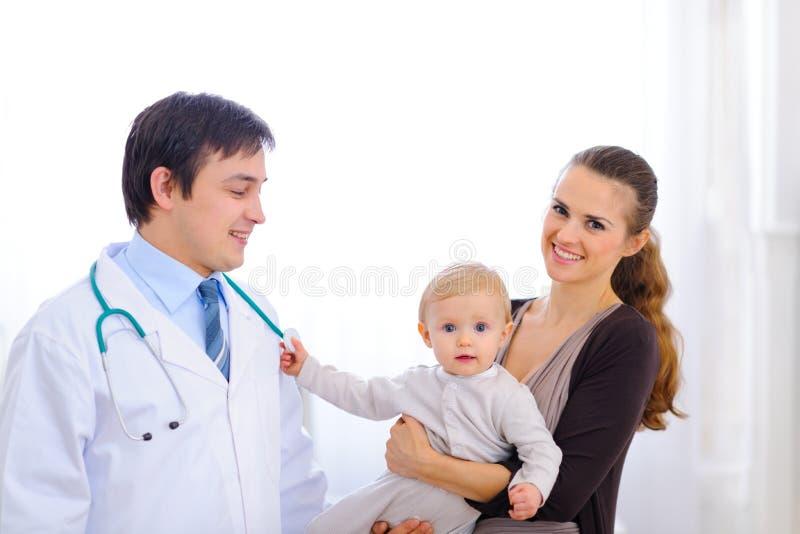 Bebê em estetoscópio tocante da mão da mamã do doutor imagens de stock