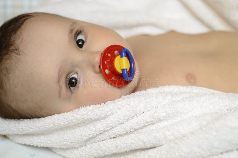 Bebê em toalhas do algodão com chupeta imagens de stock