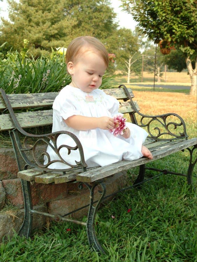 Bebê em um banco de parque imagem de stock royalty free