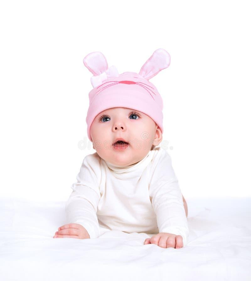 Bebê em um chapéu cor-de-rosa com as orelhas de coelho isoladas no branco fotos de stock royalty free