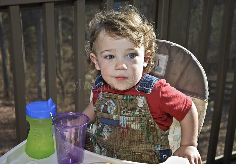 Bebê em um Highchair ao ar livre fotografia de stock