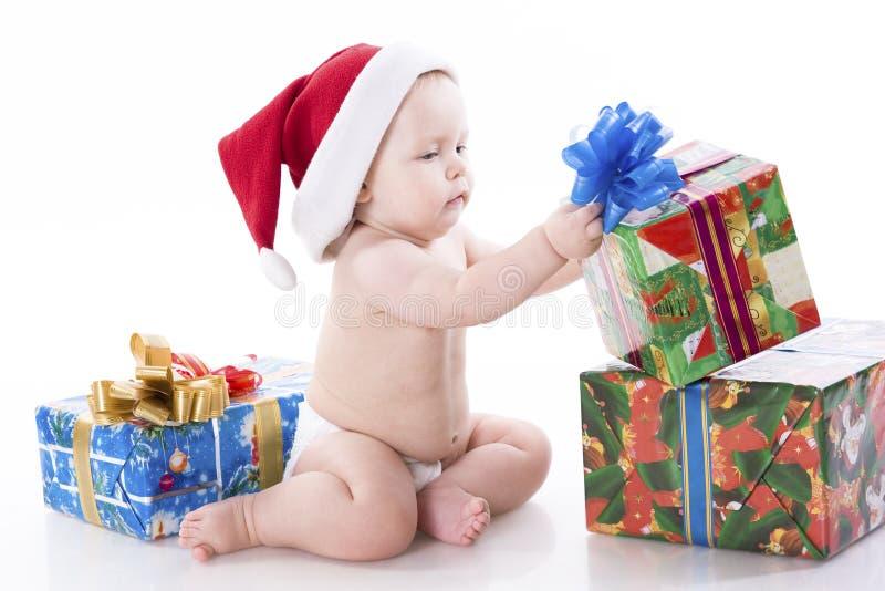 Bebê em um tampão de Papai Noel com presentes imagens de stock