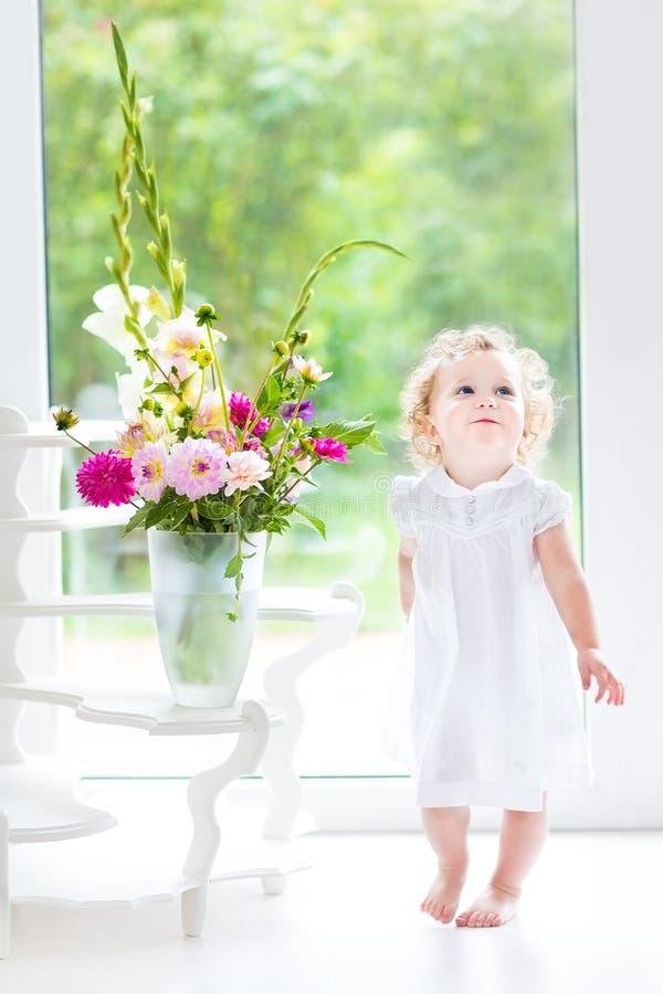 Bebê encaracolado bonito com o ramalhete da flor fresca imagens de stock royalty free