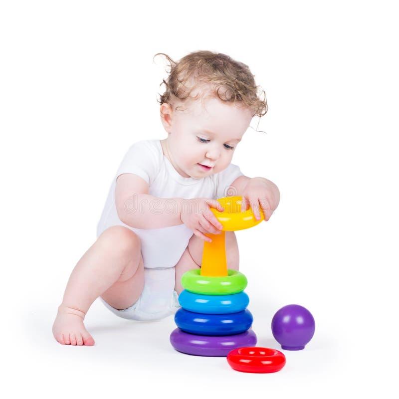 Bebê encaracolado engraçado que joga com uma pirâmide colorida fotos de stock