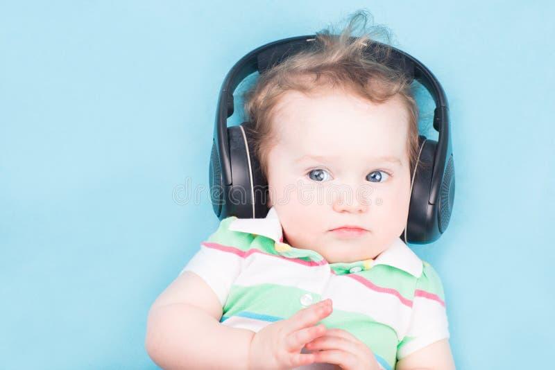 Bebê engraçado com fones de ouvido grandes foto de stock royalty free