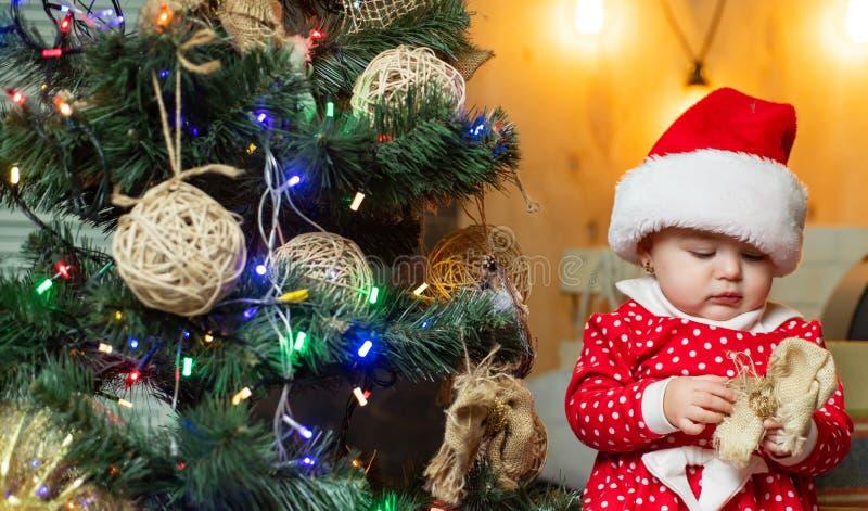 Bebê engraçado da criança com presente do Natal Crianças do Natal O bebê pequeno bonito está decorando a árvore de Natal dentro f fotografia de stock