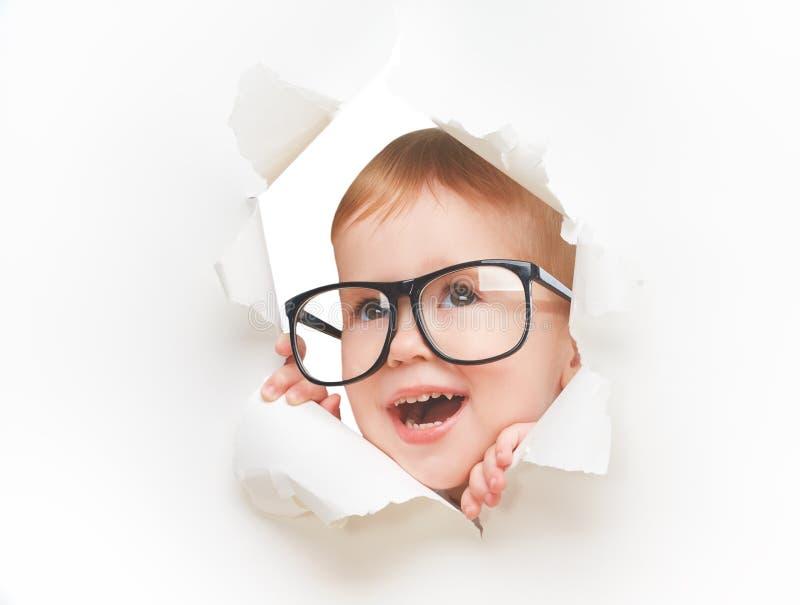 Bebê engraçado da criança com vidros que olha através do furo em um Livro Branco vazio imagem de stock
