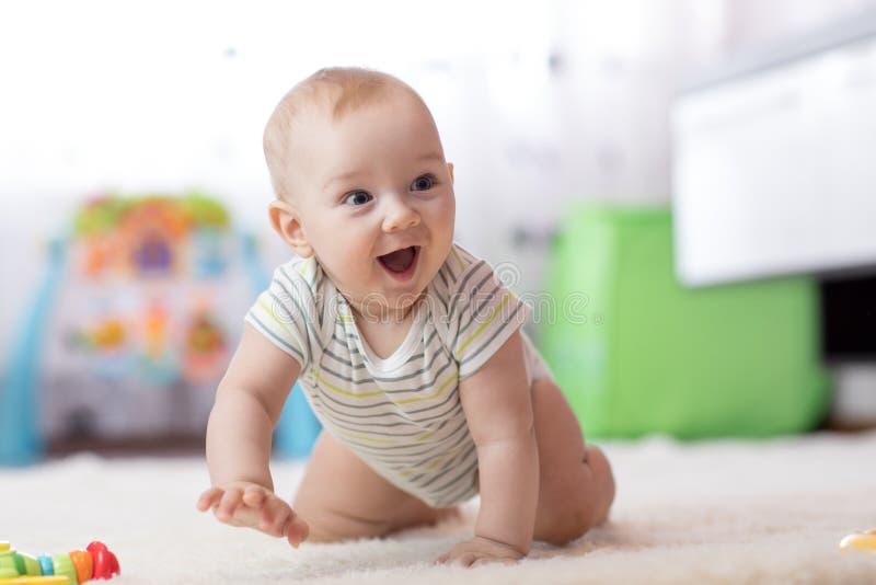 Bebê engraçado de rastejamento dentro em casa fotos de stock
