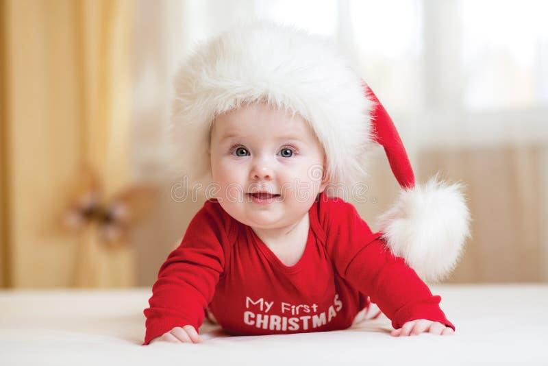 Bebê engraçado de Santa que encontra-se na cama imagens de stock