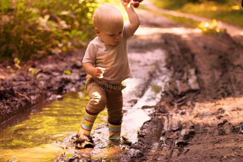 Bebê engraçado nas botas de borracha que têm o divertimento em uma poça da floresta imagem de stock