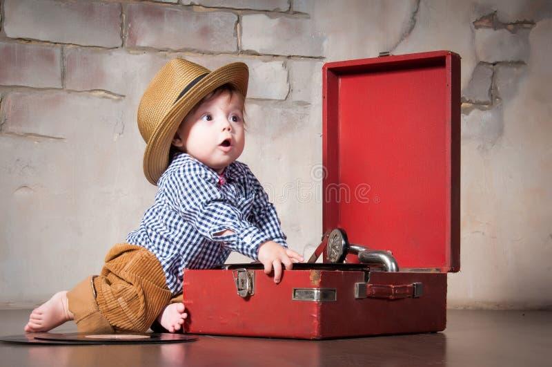 Bebê engraçado no chapéu retro com registro e gramofone de vinil imagens de stock royalty free