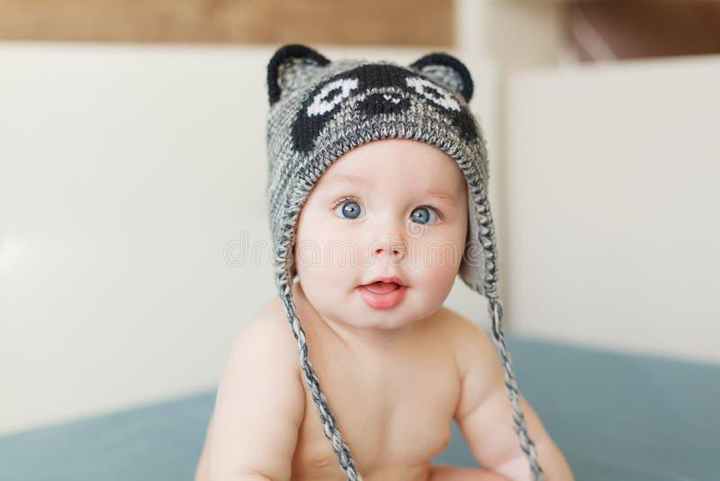 Bebê engraçado pequeno com olhos azuis grandes que sorri com o tampão bonito com as orelhas em sua cabeça imagens de stock