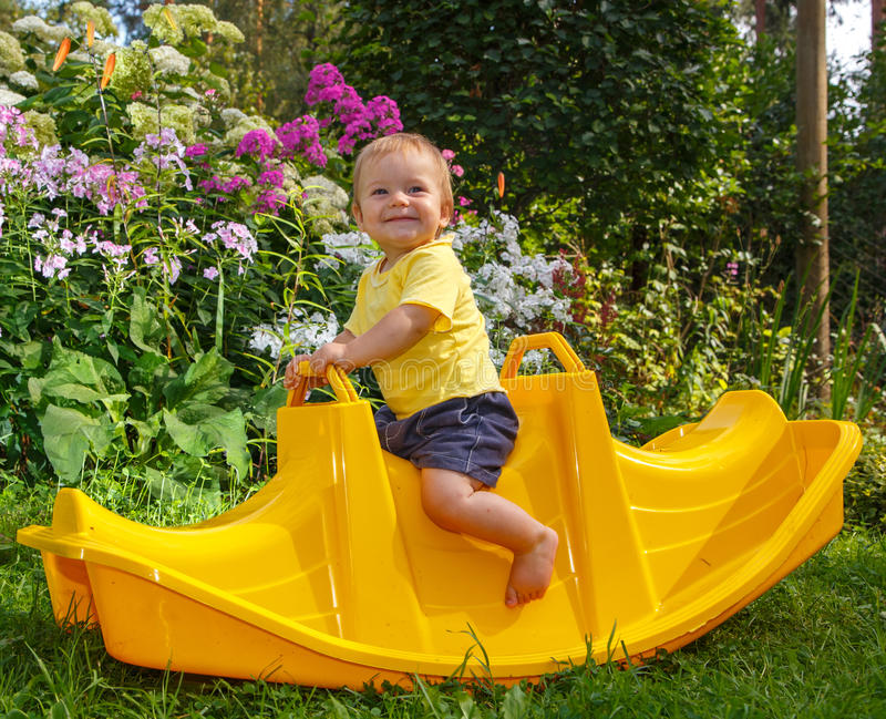 Bebê engraçado pequeno em seu balanço favorito fotografia de stock