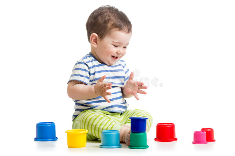 Bebê engraçado que joga com os brinquedos coloridos do copo foto de stock