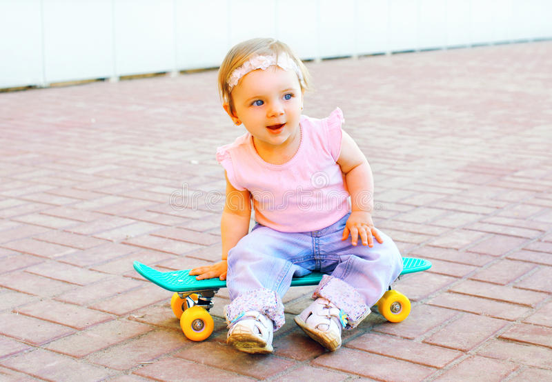 Bebê engraçado que senta-se no skate imagem de stock royalty free