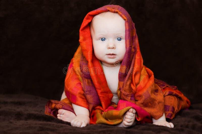 Bebê envolvido no lenço alaranjado vermelho imagem de stock royalty free