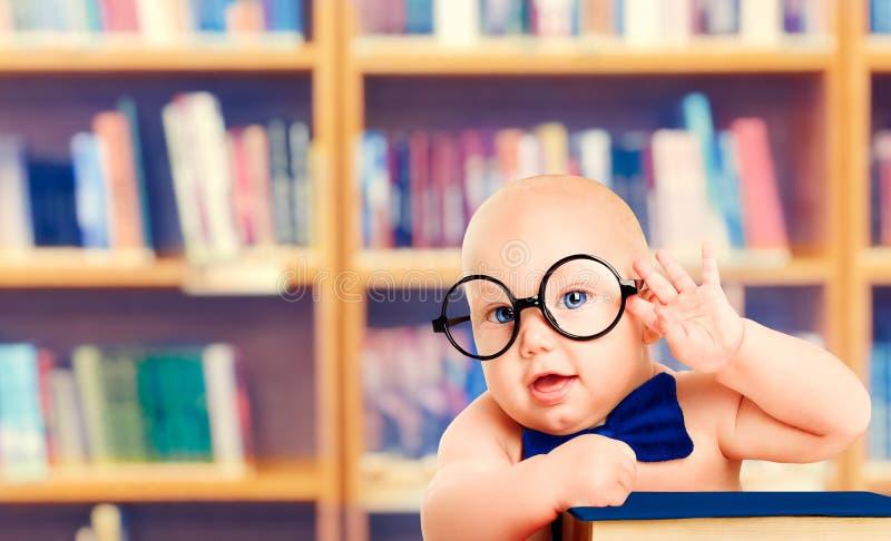 Bebê esperto nos vidros com livro, criança pequena na biblioteca escolar fotos de stock