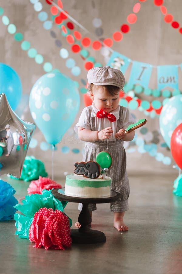 Bebê feliz adorável que come o bolo um em seu primeiro partido do cakesmash do aniversário fotos de stock