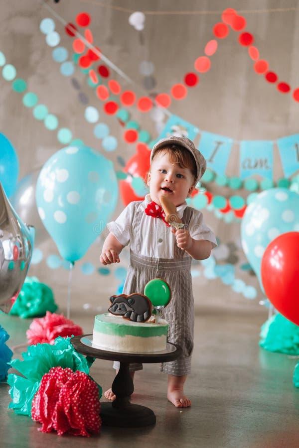 Bebê feliz adorável que come o bolo um em seu primeiro partido do cakesmash do aniversário imagens de stock