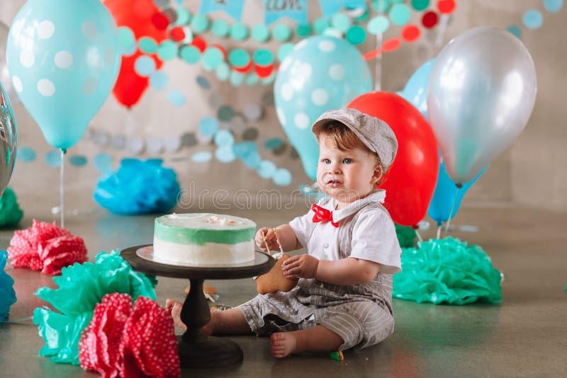 Bebê feliz adorável que come o bolo um em seu primeiro partido do cakesmash do aniversário fotografia de stock