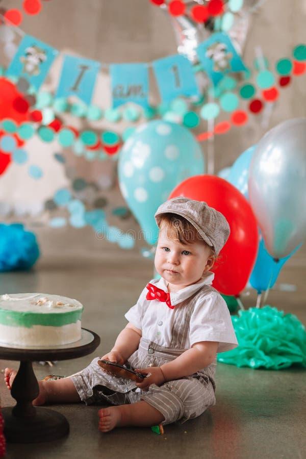 Bebê feliz adorável que come o bolo um em seu primeiro partido do cakesmash do aniversário imagens de stock royalty free