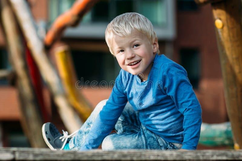 Bebê feliz bonito com o cabelo louro que tem o divertimento no campo de jogos imagens de stock