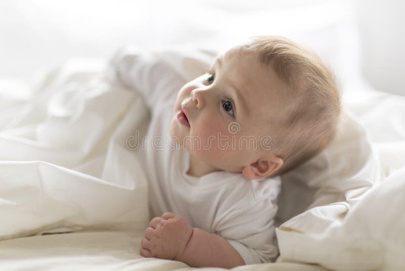 Bebê feliz bonito de 7 meses no tecido que encontra-se e que joga fotos de stock royalty free