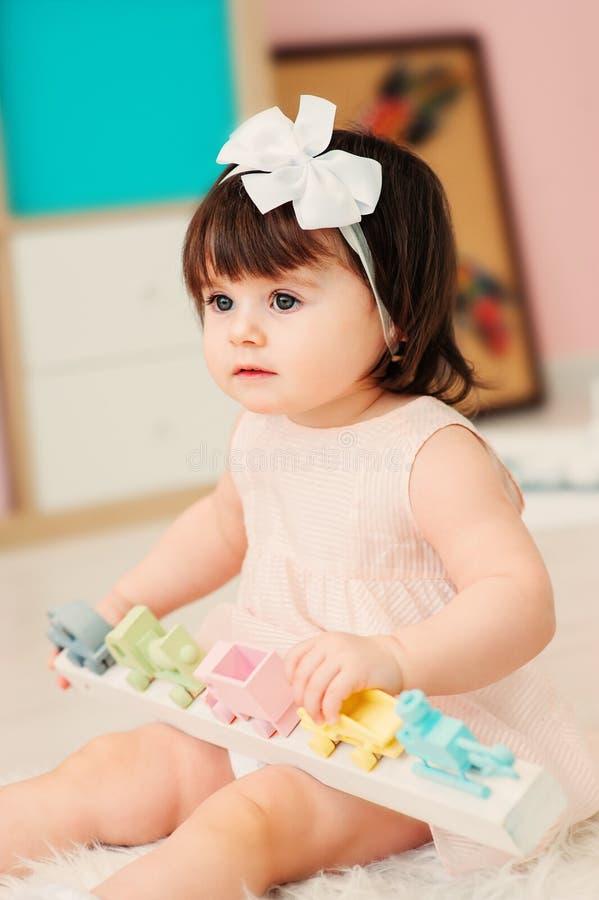 Bebê feliz bonito do bebê de um ano que joga com brinquedos de madeira em casa imagens de stock royalty free