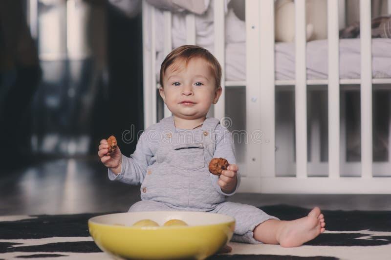 Bebê feliz bonito que come cookies em casa e que joga com a placa dos limões Captação interna do estilo de vida fotografia de stock royalty free