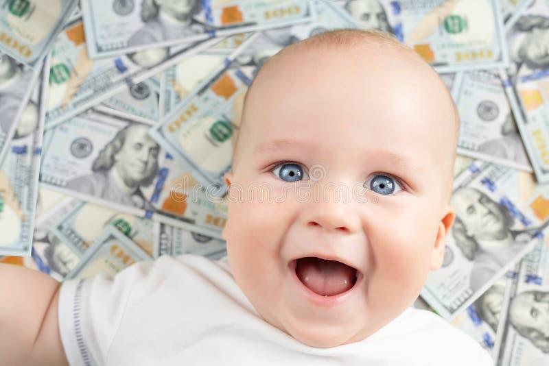 Bebê feliz bonito que sorri com cem fundos das notas de dólar Criança adorável que tem o divertimento que encontra-se sobre o ban fotografia de stock royalty free