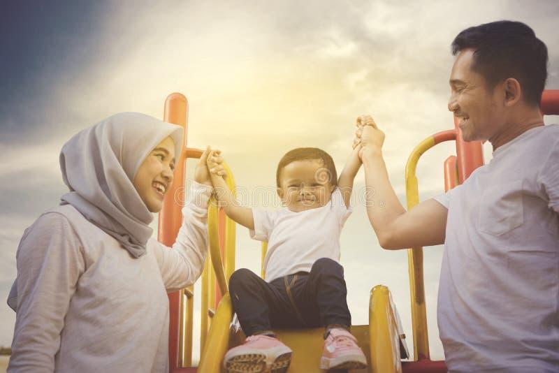 Bebê feliz com seus pais no campo de jogos imagem de stock