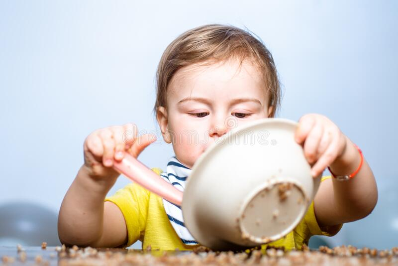 Bebê feliz com uma colher Bebê comendo Criança brinca na cozinha com pratos Bebê-colher feliz se come fotos de stock royalty free