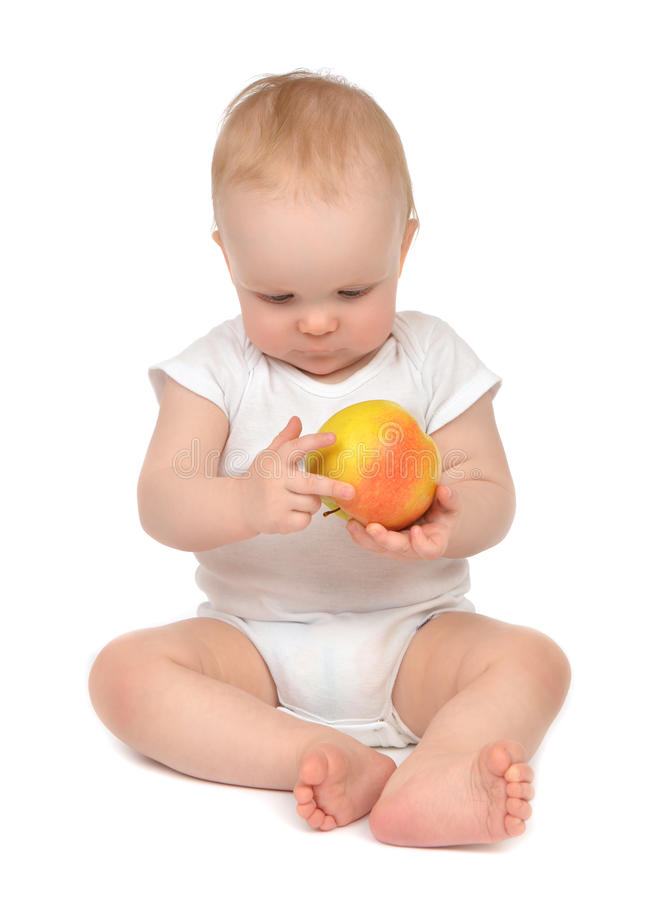 Bebê feliz da criança que senta-se no tecido e que come o amarelo vermelho app fotografia de stock