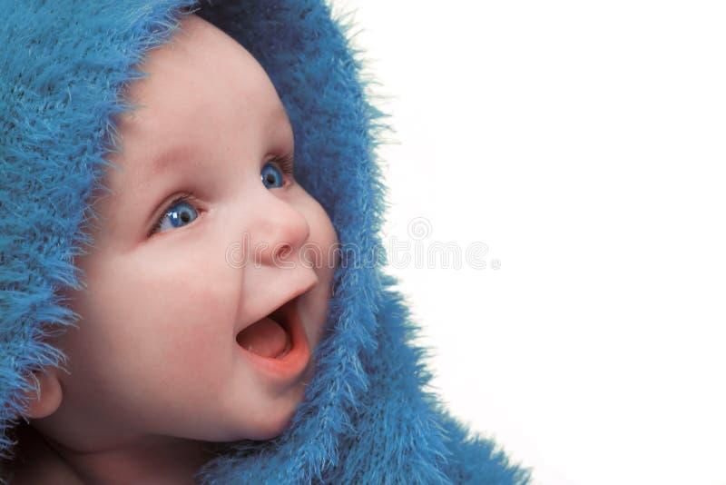 Bebê feliz de sorriso na cobertura azul fotografia de stock