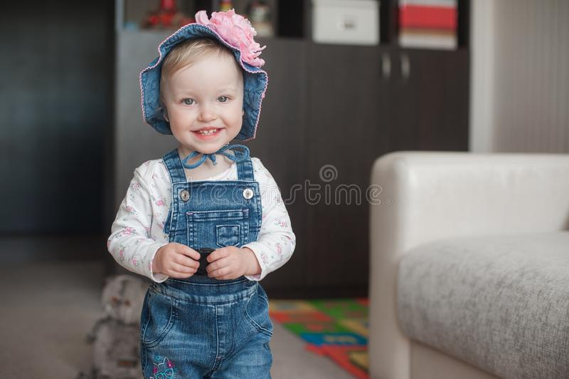 Bebê feliz de sorriso no chapéu do verão Panamá com uma flor cor-de-rosa grande Olhe a câmera fotografia de stock