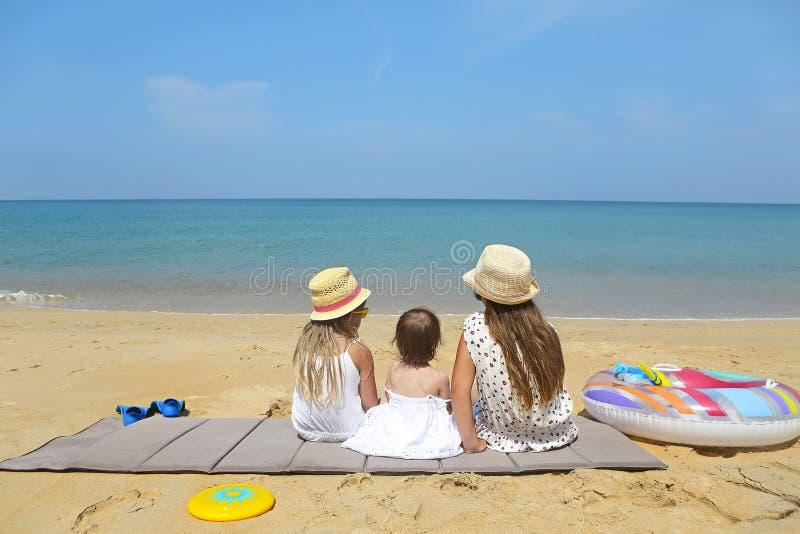 Bebê feliz e suas irmãs que jogam na areia em uma praia bonita fotografia de stock royalty free