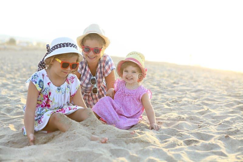 Bebê feliz e suas irmãs que jogam na areia em uma praia bonita fotografia de stock