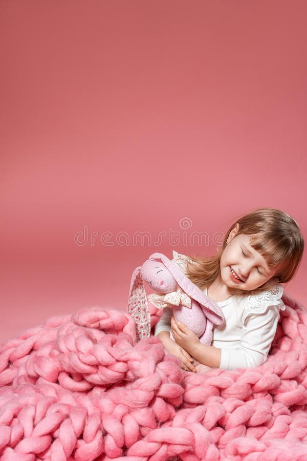 Bebê feliz no fundo coral cor-de-rosa coberto com a cobertura e Merino foto de stock royalty free