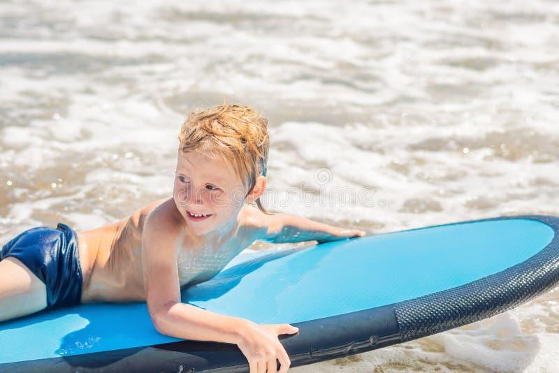 Bebê feliz - passeio novo do surfista na prancha com divertimento no mar fotos de stock